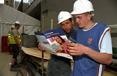Building workers in hard hats on a construction site at Canary Wharf read brochures about Learndirect basic skills courses available in the nearby Learning Centre run by the TUC, UCATT and Lewisham Co... - Janina Struk - 25-05-2004
