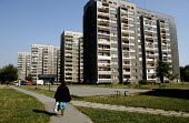 Woman with shopping walking through a housing estate, Nowa Huta, Poland, a town built around the steelworks in the 1950s - Janina Struk - 1990s,1997,blocks,bought,buy,buyer,buyers,buying,commodities,commodity,consumer,consumers,customer,customers,eastern Europe,EBF,EBF Economy,Economic,Economy,FACTORIES,factory,FEMALE,flats,footpath,foo