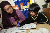 Asian woman primary school teacher in a classroom supervising a pupil who is learning to write numbers at Bigland school in east London - Janina Struk - 06-10-2005