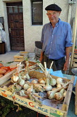 Local French farmer with beret selling onions in a weekly market in a small town. - Janina Struk - 28-08-2007