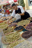 Selling black and green olives at a weekly market in a small French town. - Janina Struk - 2000s,2007,BME Black minority ethnic,buy,buyer,buyers,buying,commerce,commodities,commodity,EBF Economy,economic,economy,eu,Europe,european,europeans,farm,food,FOODS,french,fresh,goods,LAB LBR work,lo