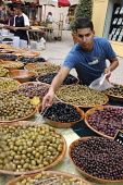 Selling black and green olives at a weekly market in a small French town. - Janina Struk - 2000s,2007,BME Black minority ethnic,buy,buyer,buyers,buying,commerce,commodities,commodity,dairy,EBF Economy,economic,economy,eu,Europe,european,europeans,farm,food,FOODS,french,fresh,goods,LAB LBR w