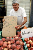 French market trader selling white peaches at a weekly market in a small town. - Janina Struk - 28-08-2007