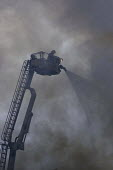 Firefighter on a hydraulic platform with a firehose fighting a blaze in dense smoke during a fire on Brixton Road. London - Janina Struk - 05-04-2008