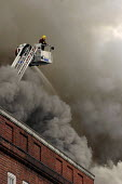 Firefighter on a hydraulic platform with a firehose fighting a blaze in dense smoke during a fire on Brixton Road. London - Janina Struk - 2000s,2008,adult,adults,cities,city,dia accident accidents,fighting,fire,fire and rescue,fire brigade,firefighter,firefighters,firefighting,fireman,firemen,fires,hose,jet,job,jobs,LAB LBR Work,ladder,