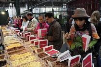 Customers buying chocolate at a stall in Borough Market, London. - Janina Struk - 21-06-2008