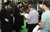 A crowd gathers to speak to Rabbi Yisroel Dovid Weiss and the Jews against Zionism and the state of Israel from the organization Neturei Karta International at the Islam Expo, Olympia, London. - Janina Struk - ,2000s,2008,against,anti-Zionist,BME Black minority ethnic,BME minority ethnic,communicating,communication,conversation,conversations,dialogue,discourse,discuss,discusses,discussing,discussion,faith,i