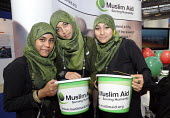 Young women wearing the hijab from the charity Muslim Aid at a stall at the Islam Expo, Olympia, London. - Janina Struk - &,2000s,2008,ace culture,aid,assistance,belief,BME Black minority ethnic,bucket,buckets,charitable,charities,charity,cities,city,collecting,conviction,dress,faith,FEMALE,giving,GOD,hajib,headscarf,hel