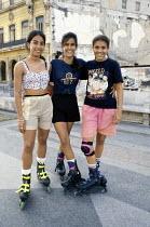 Girls wearing rollerblades in the streets of Havana. - Janina Struk - 1990s,1997,activities,adolescence,adolescent,adolescents,americas,caribbean,cities,city,cuba,cuban,cubans,EMOTION,EMOTIONAL,EMOTIONS,female,females,friend,friends,friendship,friendships,girl,girls,hav