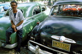 A taxi driver with his American classic car, parked in the streets of Havana. - Janina Struk - 1990s,1998,American,americans,americas,AUTO,AUTOMOBILE,AUTOMOBILES,AUTOMOTIVE,cab,cabs,car,caribbean,cars,cas,cities,city,classic,cuba,cuban,cubans,driver,drivers,DRIVING,EBF,Economic,Economy,LAB LBR