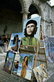 Paintings of Che Guevara alongside those depicting naked women, at a stall in Plaza de la Catedral (Cathedral Square),Havana - Janina Struk - 1990s,1997,ace arts culture,americas,art,artwork,artworks,attraction,attractions,bare,bought,buy,buyer,buyers,buying,canvas canvases,caribbean,Che Guevara,cities,city,commodities,commodity,consumer,co