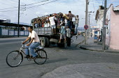 A man riding a bicycle and a crowd packed into a open-backed truck, a popular form of transport in Cuba (due to the shortage of fuel). - Janina Struk - 1990s,1997,americas,bicycle,bicycles,BICYCLING,Bicyclist,Bicyclists,bike,bikes,caribbean,cities,city,crowd,crowded,crowds,cuba,cuban,cubans,cycle,cycles,cycling,cyclist,cyclists,EBF,EBF Economy,Econom