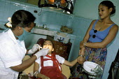 A dentist performing a dental checkup on a schoolgirl, at a Polyclinic in Havana. - Janina Struk - 1990s,1997,adult,adults,americas,and,care,carer,carers,caribbean,carrier,carriers,chair,chairs,check,checking,checkup,checkups,child,childcare,CHILDHOOD,CHILDMINDING,children,cities,city,clinic,clinic