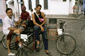 Young men and their bicycle taxis, waiting for passengers. - Janina Struk - 1990s,1997,americas,attraction,attractions,bicycle,bicycles,BICYCLING,Bicyclist,Bicyclists,bike,bikes,cab,cabs,caribbean,cas,cities,city,colleague,colleagues,cuba,cuban,cubans,customer,customers,cycle
