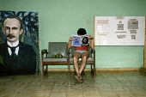 A man reading the magazine Cuba Ci, at the Brigadista Brigade camp outside Havana. Where foreign supporters of Cuba, work on the seasonal fruit farms. - Janina Struk - 1990s,1997,americas,art,artwork,artworks,bench,benches,Brigadista,camp,camps,caribbean,chair,chairs,cities,city,Cuba,cuban,cubans,Cubasi,farm,farms,foreign,foreigner,foreigners,fruit,FRUITS,internatio
