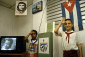 Cuban boys in uniform standing guard and saluting to the flag, alongside a ballot box on election day. On the television is a film featuring Paul Robeson. - Janina Struk - 1990s,1998,activist,activists,americas,ballot,Ballot Box,BALLOTING,ballots,box,boxes,boy,boys,CAMPAIGN,campaigner,campaigners,CAMPAIGNING,CAMPAIGNS,caribbean,Che,child,CHILDHOOD,children,cities,city,c