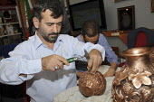 An Iranian man hand engraving a copper vase at the Islam Expo at Olympia in London. - Janina Struk - 11-07-2008