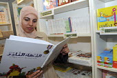 A woman wearing a hijab reads an illustrated Arabic language book for children at Palm tree book shop at the Islam Expo at Olympia, London. - Janina Struk - 11-07-2008