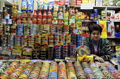 A stall holder and a colourful display of tinned food and displayed prices at an indoor market in Riga. - Janina Struk - 30-03-2009