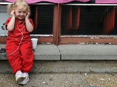 A young child smiles as she listens to an iPod personal stereo system. London - Janina Struk - 15-06-2009