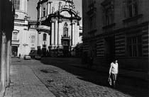 Elderly woman walking down a cobbled street past an imposing catholic church, Lviv, Ukraine - Janina Struk - 15-09-1996