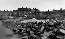 A man walks across a demolition site due for regeneration, Halifax - Janina Struk - 1990s,1996,brick,bricks,building,buildings,cities,city,debris,demolish,DEMOLISHED,demolishing,demolition,derelict,DERELICTION,developer,developers,development,EBF Economy,EQUALITY,excluded,exclusion,H