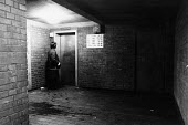 A woman alone waiting for a lift, late at night in a badly lit area of a block of council flats. - Janina Struk - 1980s,1983,ACE,alone,architecture,basement,basements,blocks,buildings,cities,city,council,culture,dangerous,dark,FEMALE,flat,flats,hazard,hazardous,HAZARDS,High Rise,housing,lift,lifts,local authority