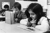An girl and a boy reading at a shared desk in a school classroom. - Janina Struk - 1980s,1981,asian,asians,BAME,BAMEs,black,bme,BME minority ethnic,bmes,book,books,boy,boys,child,CHILDHOOD,children,class,classroom,classrooms,diversity,edu education,education,educational,ethnicity,fe