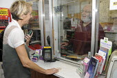 A customer sends a package from a small village post office and exchanges a few words with the postmaster serving behind the counter. Cornwall - Janina Struk - 18-09-2009