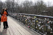 A heterosexual young couple kiss on Chortov Bridge, or The Bridge of Love, bridge in a Kiev city park where lovers lock padlocks to the bridge and throw away the key as a symbol of their love and comm... - Janina Struk - 2010s,2012,ACE,adult,adults,boyfriend,BOYFRIENDS,Bridge,cities,city,couple,COUPLES,culture,EMBRACE,EMBRACING,EMOTION,EMOTIONAL,EMOTIONS,engaged,engagement,enthusiasm,enthusiastic,Europe,female,girlfri