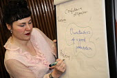 A tutor writing on a flip chart, characteristics of a good presentation, while teaching a workshop on Presentation Skills at BECTU Women's conference. - Janina Struk - 2010s,2012,activist activists,adult adults,adult education,bectu,board,class,communicating,communication,conversation,conversations,dialogue,discourse,DISCUSS,discusses,discussing,discussion,female,le