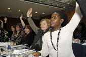 A black woman UCU delegate voting with colleagues at Women's TUC, 2015 - Janina Struk - 13-03-2015