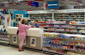 A woman dressed in pink shopping at the Pharmacy counter a Sainsbury's supermarket in Hazel Grove. - John Sturrock - 10-10-2002