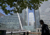 The silhouette of a man walking beneath leafy branches in front of a pedestrian bridge and bright sunlight office blocks at Canary Wharf, Docklands, London - John Sturrock - 30-07-2004