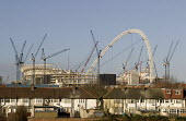 Cranes surrounding the steel shell and arch of the new Wembley Stadium as it rises above nearby houses during the construction, London - John Sturrock - 12-01-2005