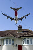 Large four engined passenger aircraft, flying low over suburban house roof, shortly before landing at Heathrow Airport London - John Sturrock - 07-04-2005