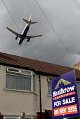 A two engined British Airways passenger aircraft, flying low over suburban house roof, shortly before landing at London Heathrow Airport. A For Sale sign is displayed outside the house - John Sturrock - 07-04-2005