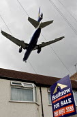 A two engined British Airways passenger aircraft, flying low over suburban house roof, shortly before landing at London Heathrow Airport. A 'For Sale' sign is displayed outside the house - John Sturrock - 07-04-2005