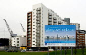 A sign for Glasgow Harbour in front of a new residential block of flats and traditional quayside cranes. This development is Phase 1 of the regeneration of the north bank of the River Clyde - John Sturrock - 2000s,2005,ACE,apartment,apartments,architecture,bank,BANKS,block,blocks,building,buildings,cities,city,communicating,communication,condominium,Construction Industry,crane,cranes,culture,developer,dev