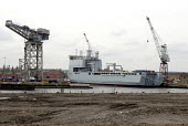 The construction of HMS Daring, the first of the new Type 45 class of Anti-Air Warfare Destroyer for Royal Navy, at BAE Systems Naval Ships yard on the River Clyde at Govan, Glasgow. Looking across th... - John Sturrock - 2000s,2005,Armaments,arms,BAE,bank,BANKS,boat,boats,capitalism,capitalist,crane,cranes,Destroyer,dock,docks,dockside,Dockyard,dockyards,EBF,EBF Economy,Economic,Economy,Engineering,Glasgow,harbor,harb