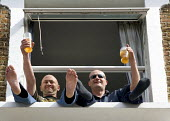 Two men, holding partially drunk pint glasses of lager, sitting and waving, with their feet out of a first floor window - John Sturrock - 18-05-2005
