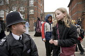 A police sergeant talks to a schoolgirl outside a school in Acton, west London - John Sturrock - 2000s,2006,adult,adults,beat,child,CHILDHOOD,children,cities,city,clj,communicating,communication,communities,community,conversation,dialogue,edu education,female,females,force,gate,gates,girl,girls,j