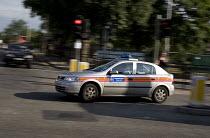 A Metropolitan police car speeding though a traffic light controlled junction in Ealing - John Sturrock - 30-07-2004