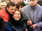 A young woman cries at the funeral of her brother, a policeman killed by the KLA. Pech, Serbia. 1998 - Andrija Ilic - 1990s,1998,adult,adults,Balkan,balkans,conflict,conflicts,europe,FEMALE,force,funeral,FUNERALS,male,man,men,OFFICER,OFFICERS,people,person,persons,POLICE,policeman,POLICEMEN,POLICING,serb,serbia,Serbi