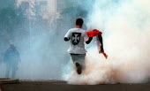 Demonstrator running through a cloud of tear gas during clashes as the Miloshevic regime falls. Belgrade, Serbia. 2000 - Andrija Ilic - 01-07-2000