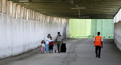 A Palestinian family walk through the security tunnel at the Erez border between Gaza Strip and Israel. Gaza 2005 - Andrija Ilic - 06-07-2005
