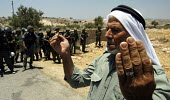 A Palestinian prays in front of Israeli troops during a joint protest with Israeli and Palestinian activists against the controversial Israeli barrier wall, village of Bilin, West Bank 2005 - Andrija Ilic - 11-07-2005