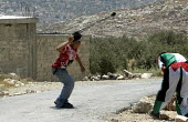 Palestinians throwing stones with slings at Israeli troops during a joint protest by Israeli, Palestinian and international peace activist against the controversial Israeli barrier wall, village of Bi... - Andrija Ilic - 09-07-2005