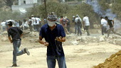 Palestinians throw stones with slings at Israeli troops during a joint protest by Israeli, Palestinian and international activists against the controversial Israeli barrier wall in the village of Bili... - Andrija Ilic - 11-07-2005