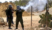 Israeli soldiers firing tear gas against Palestinians during a protest against the construction of the controversial Israeli fence and wall. Bilin, West Bank 2005. Firing a Armsel Striker 12 bore shot... - Andrija Ilic - 26-08-2005